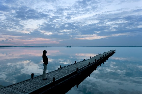 Woman on dock at lake (iStockphoto)
